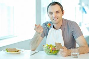 Ung mann spiser med serviett som beskytter klærne