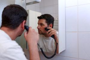 Mann som barberer seg foran speilet.