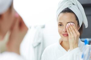 Kvinne fjerner øeysminke foran speilet.